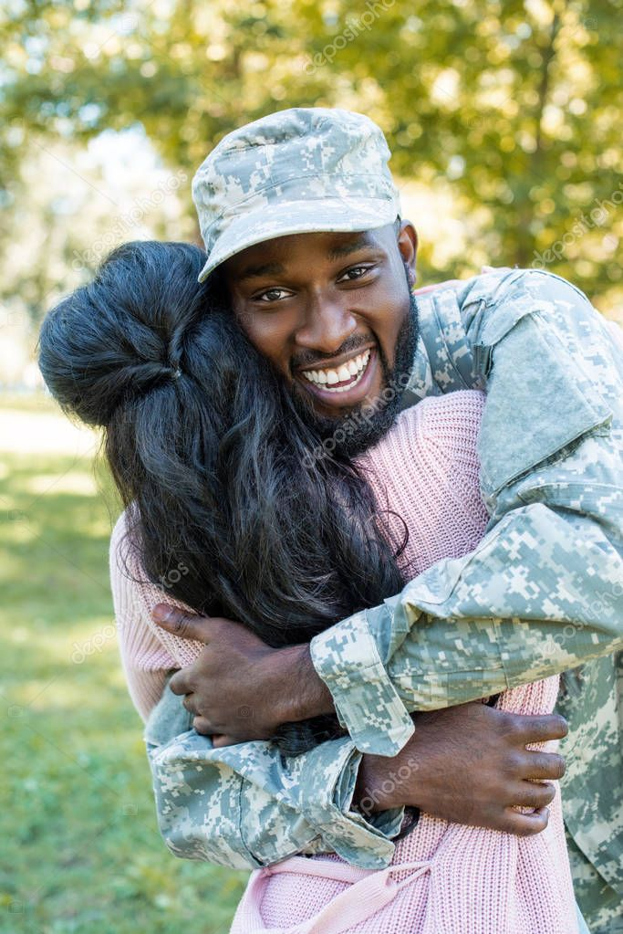 happy african american soldier in military uniform hugging girlfriend in park