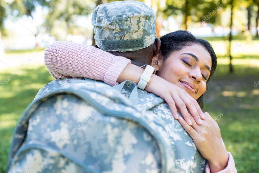 african american soldier in military uniform hugging happy girlfriend in park