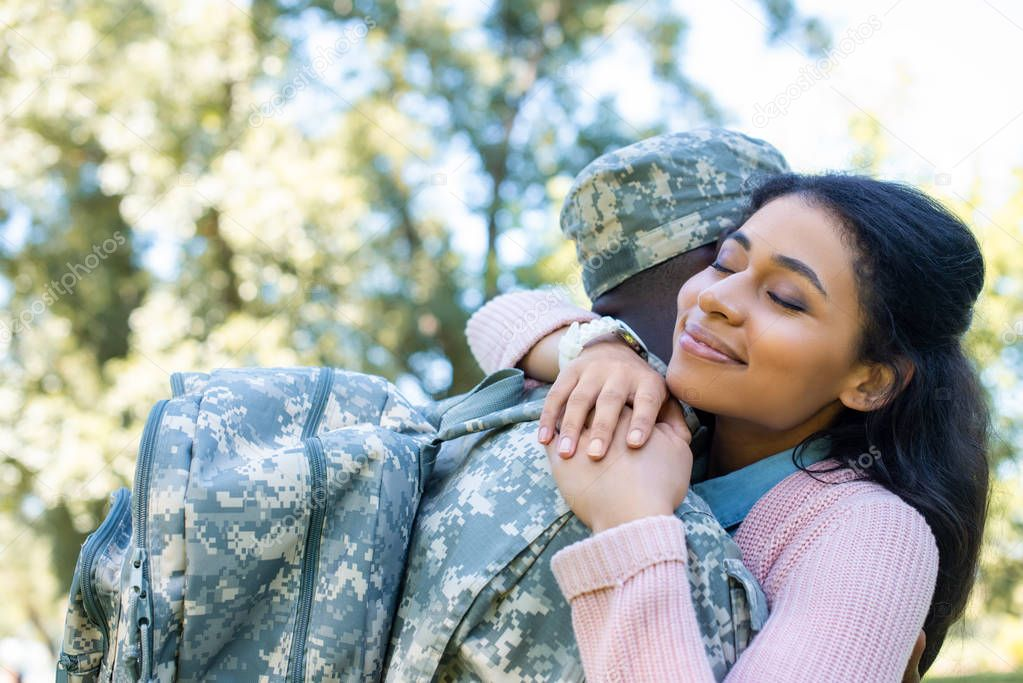 african american soldier in military uniform hugging girlfriend in park