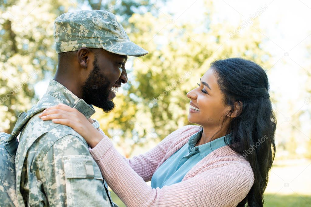 side view of smiling african american soldier in military uniform hugging girlfriend in park