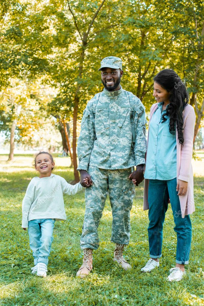 happy african american soldier in military uniform holding hands with daughter and wife in park