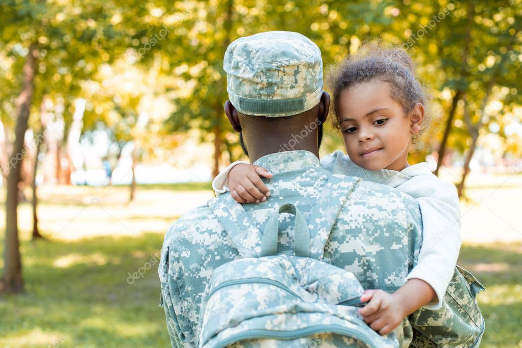 african american soldier in military uniform holding daughter in park