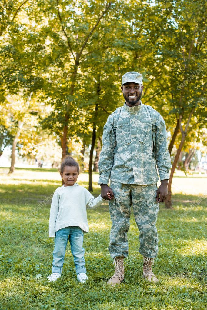 smiling african american soldier in military uniform and daughter holding hands in park