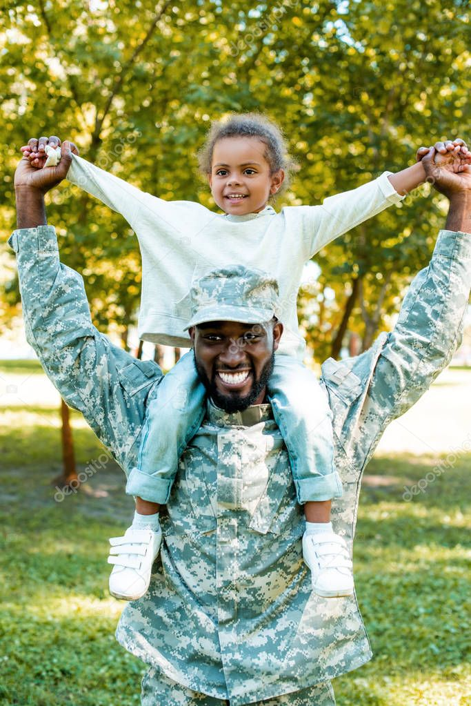 happy african american soldier in military uniform holding daughter on shoulders in park