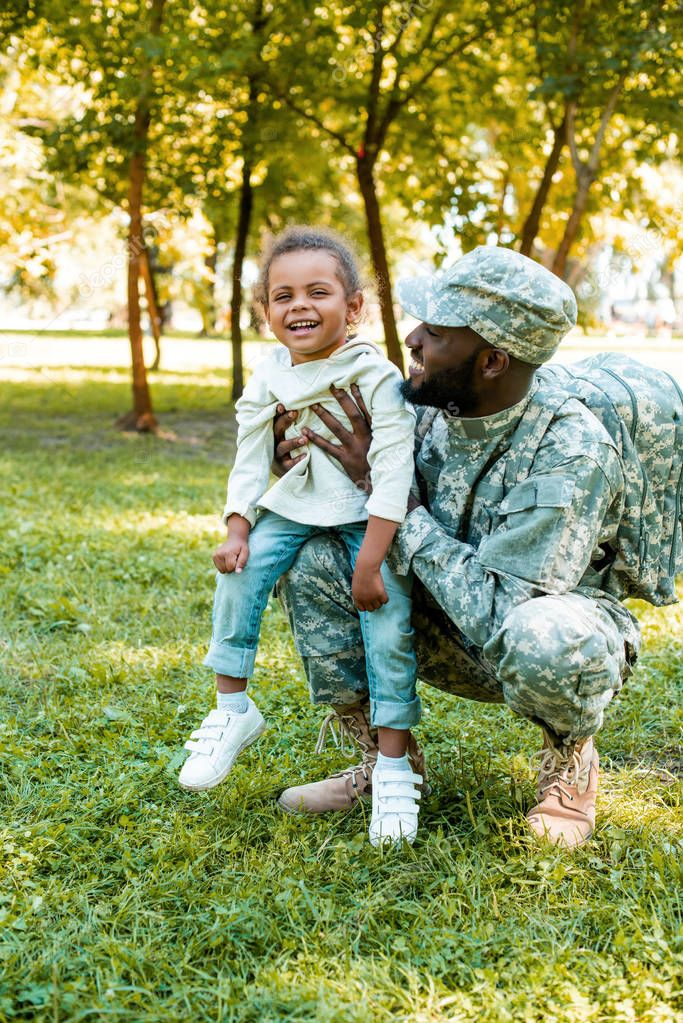 smiling african american soldier in military uniform holding happy daughter in park