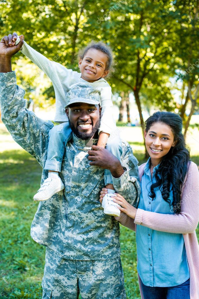 smiling african american soldier in military uniform holding daughter on shoulders in park