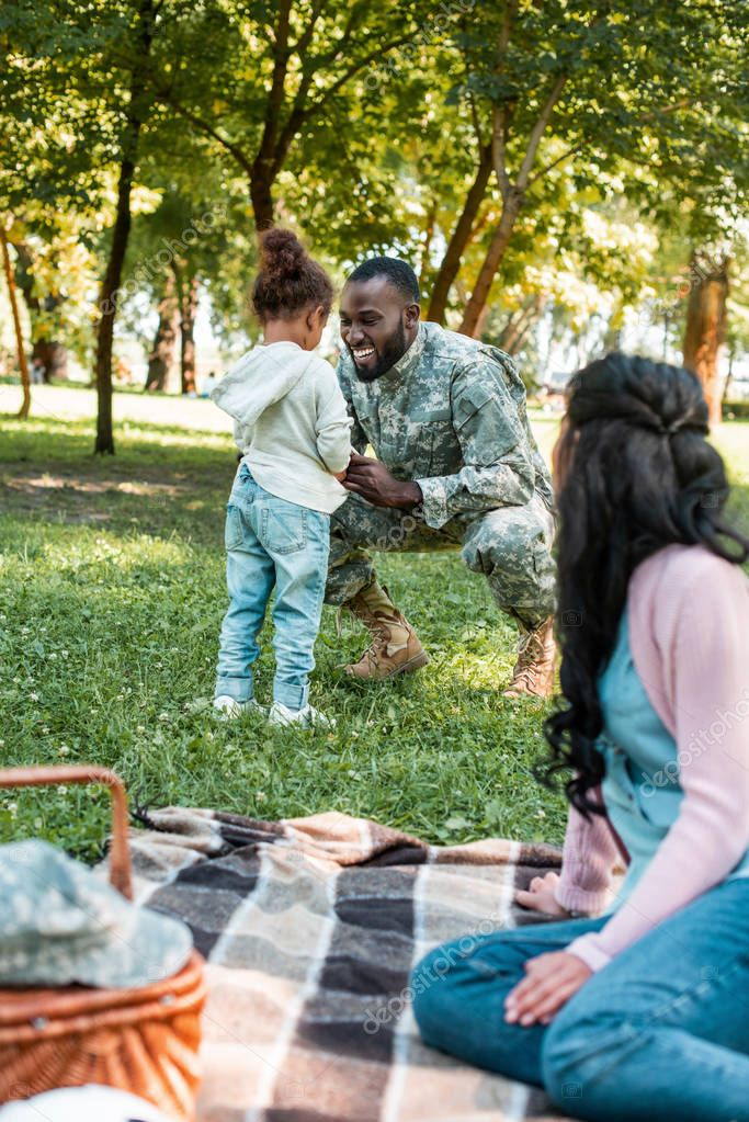 smiling african american soldier squatting near daughter in park