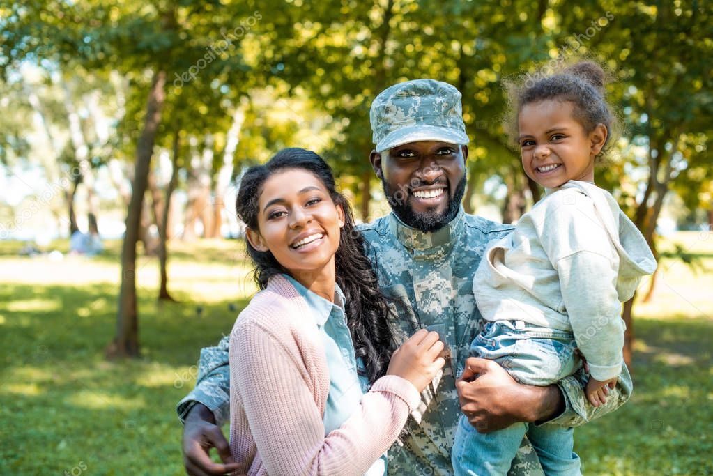 happy african american soldier in military uniform looking at camera with family in park