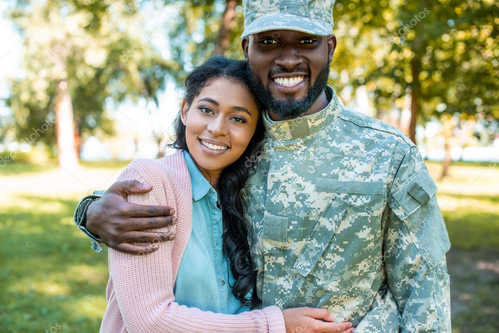 smiling african american soldier in military uniform hugging girlfriend in park