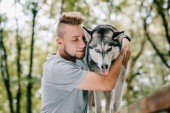 Photo young man hugging husky dog in park