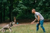 Photo young man throwing ball to husky dog in park
