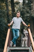 Photo young man posing on stairs with husky dog