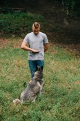 Photo man and husky dog training stand command with hand gesture