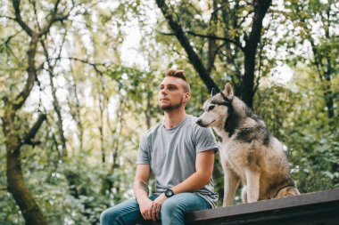 handsome man with siberian husky dog sitting in park