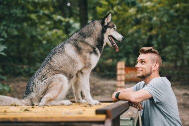 young man looking at siberian husky dog