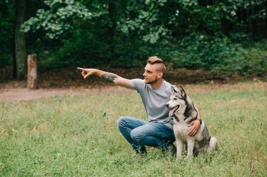 young man showing something to siberian husky dog in park