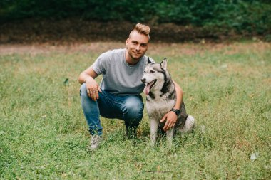 young man hugging with siberian husky dog in park