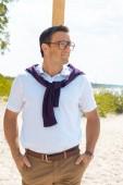 portrét usmívající se muž v brýlích na písečné pláži
