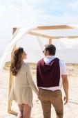 Fotografie zadní pohled na šťastný pár na písečné pláži s bílým závěsem krajky dekorace