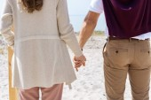 Fotografie partial view of couple holding hands while walking on sandy beach