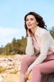atraktivní žena odpočívá na skalách na písečné pláži