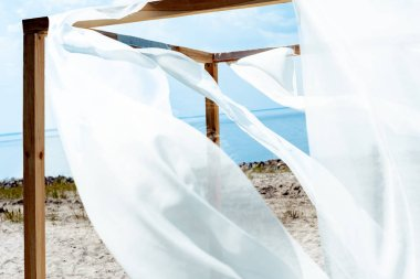 close up view of wooden decoration with white curtain lace, blue cloudy sky and river on background