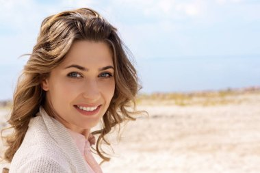 portrait of smiling woman looking at camera on sandy beach