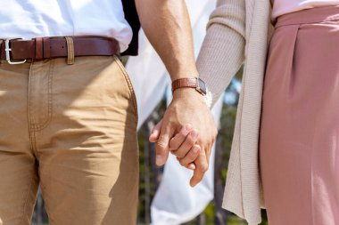 partial view of couple holding hands