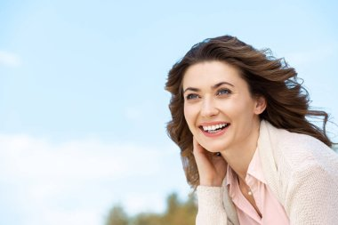 portrait of smiling beautiful woman with blue cloudy sky on background