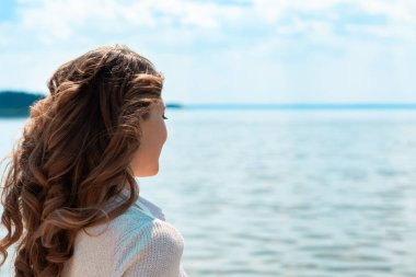 partial view of woman with sea on background