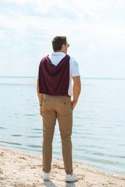 back view of stylish man standing on sandy riverbank alone