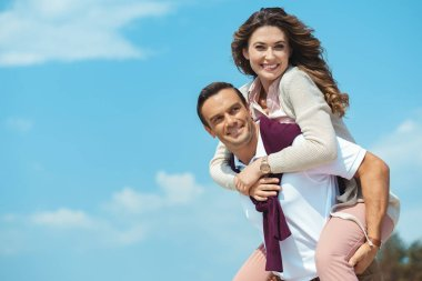 cheerful couple piggybacking together with blue cloudy sky on background