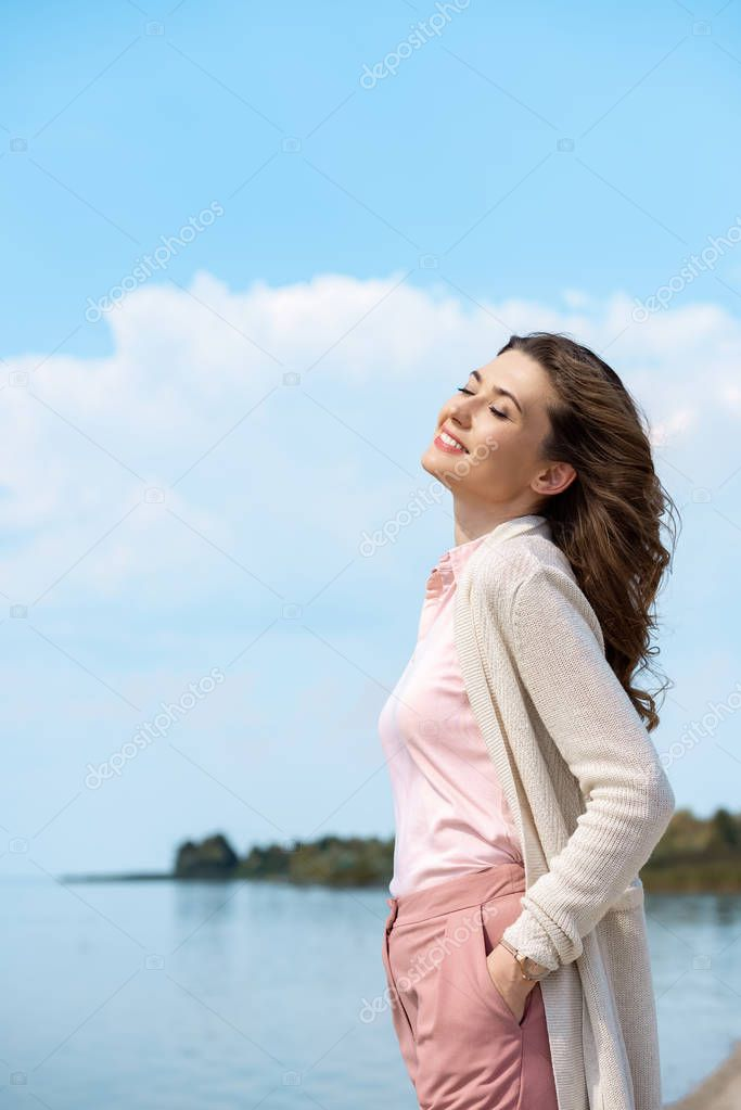 side view of beautiful smiling woman with river on background