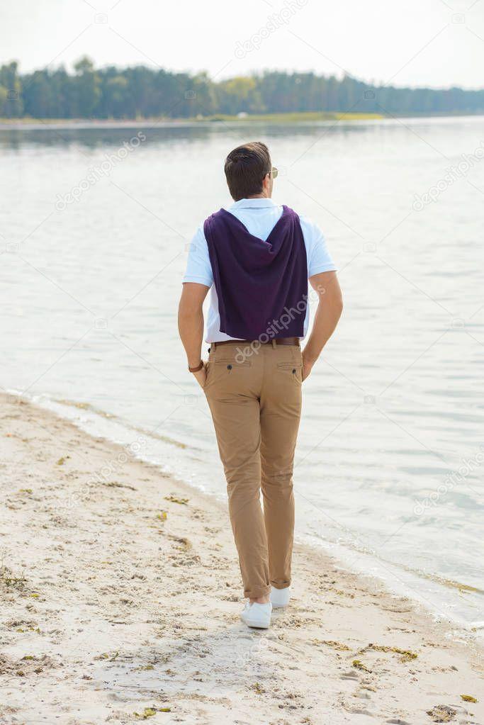 back view of stylish man walking alone on sandy riverbank