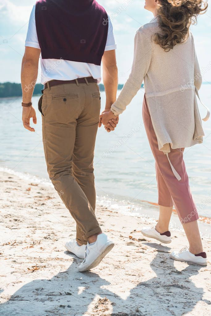partial view of romantic couple holding hands while walking on sandy riverside