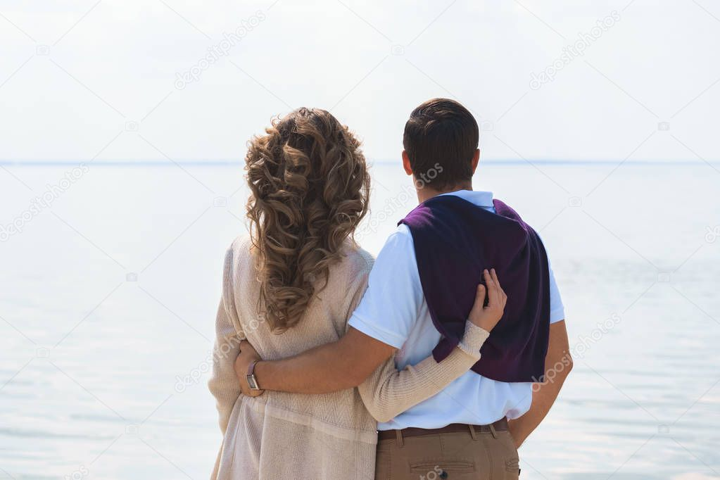 back view of romantic couple hugging and looking at sea