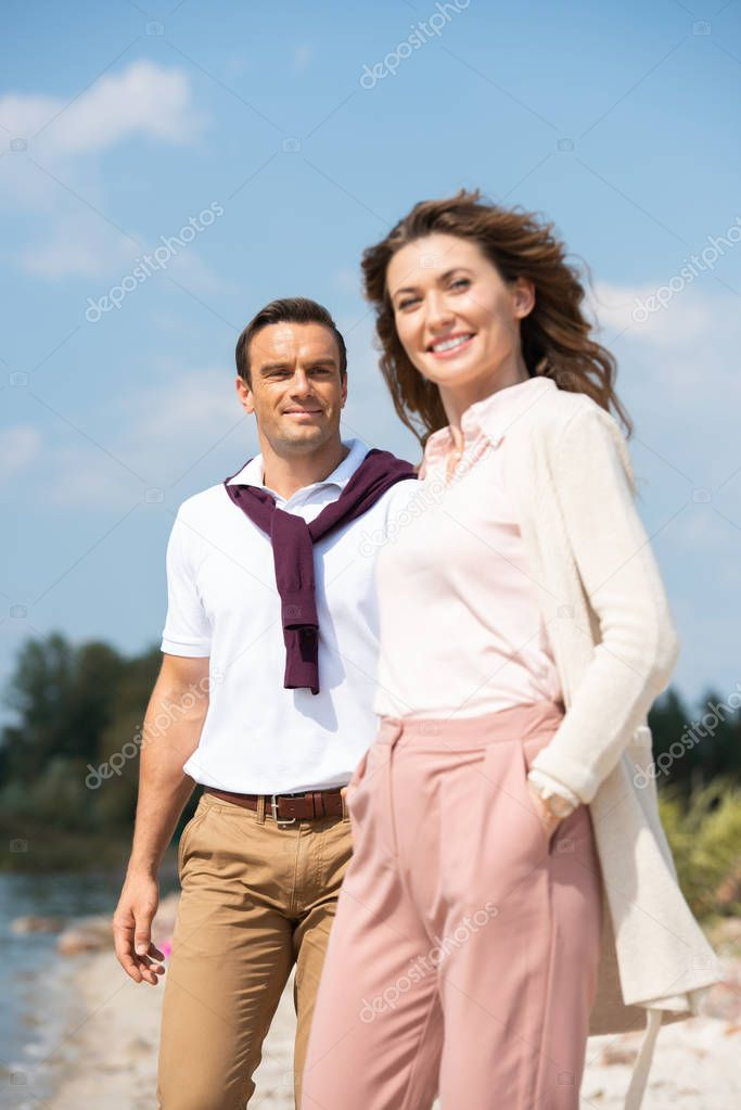 portrait of cheerful couple with blue sky on background