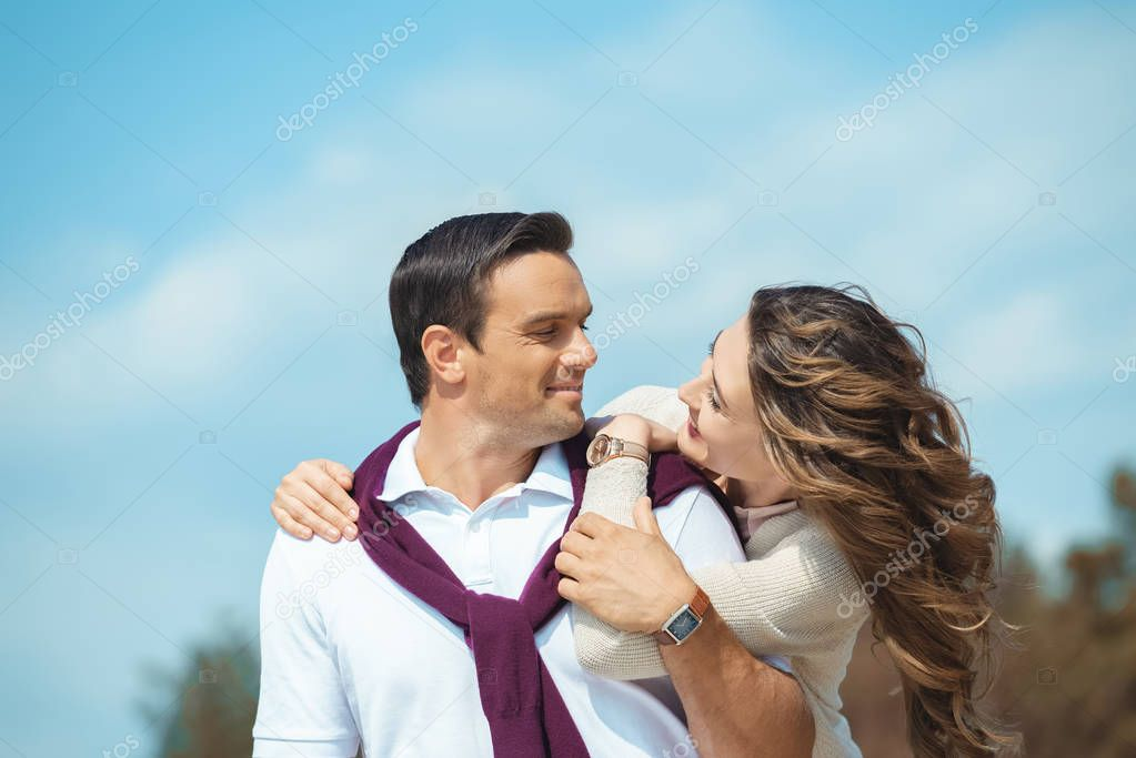 portrait of cheerful couple looking at each other with blue sky on background