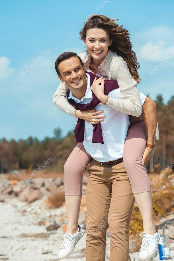 cheerful couple piggybacking together on sandy beach