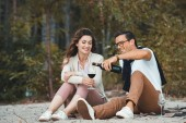 man pouring red wine into glass while resting together with wife on sandy beach