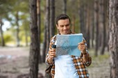 portrait of smiling tourist with map and coffee to go in forest