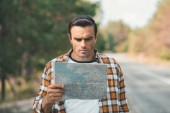 Fotografie portrait of concentrated tourist looking at map while standing on road