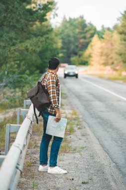side view of man with backpack and map standing on road while traveling alone