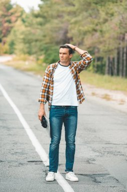 man with binoculars and map standing on road while traveling alone