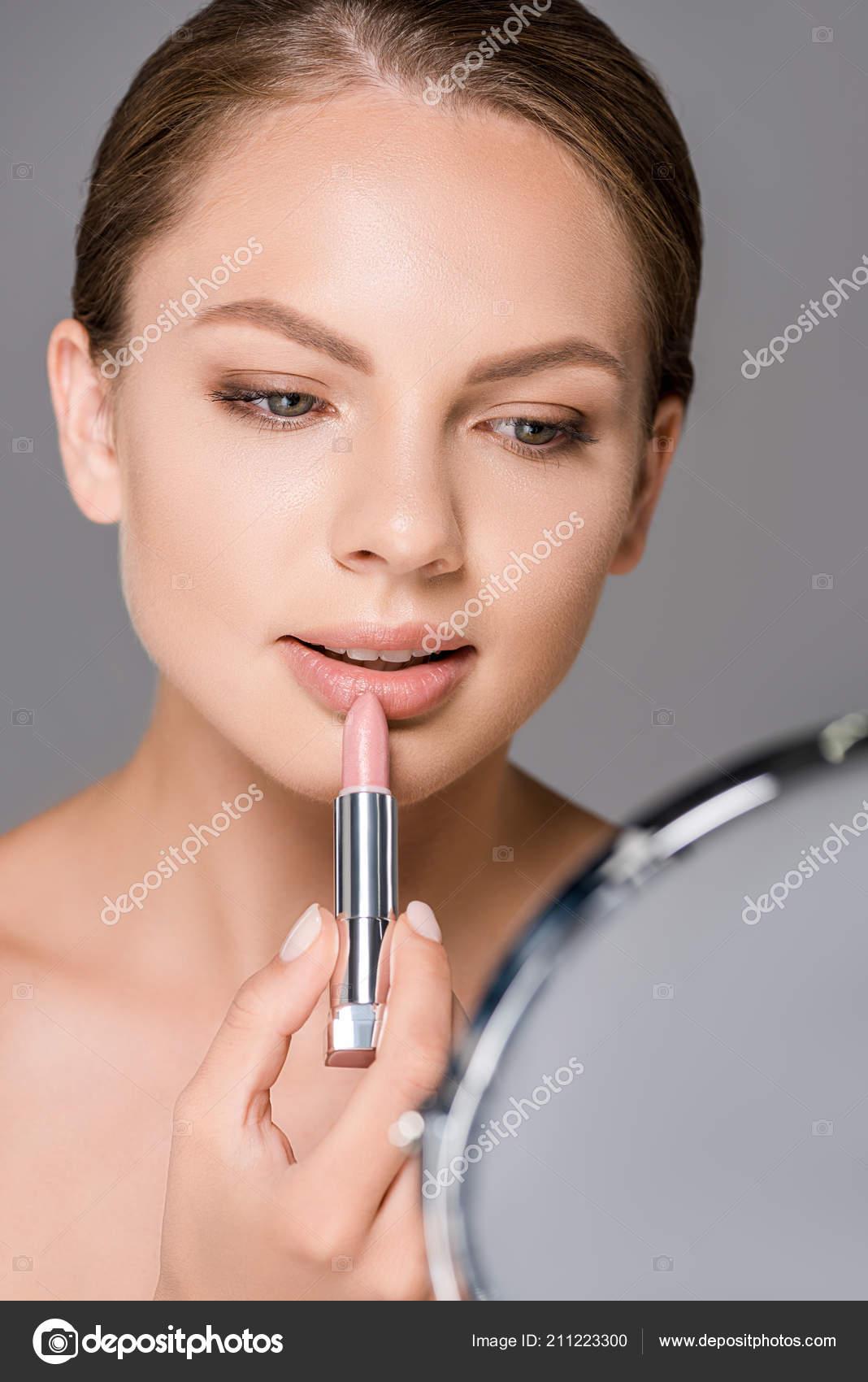 nude girl putting on lipstick