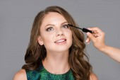 partial view of makeup artist applying mascara on models eyelashes isolated on grey