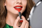 cropped shot of woman looking at mirror while applying red lipstick isolated on grey