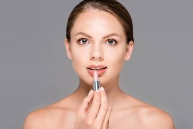 portrait of young woman applying nude lipstick isolated on grey