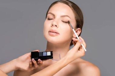 cropped shot of makeup artist applying eyeshadows on models eyelid isolated on grey