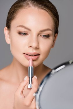 portrait of young woman with mirror applying nude lipstick isolated on grey